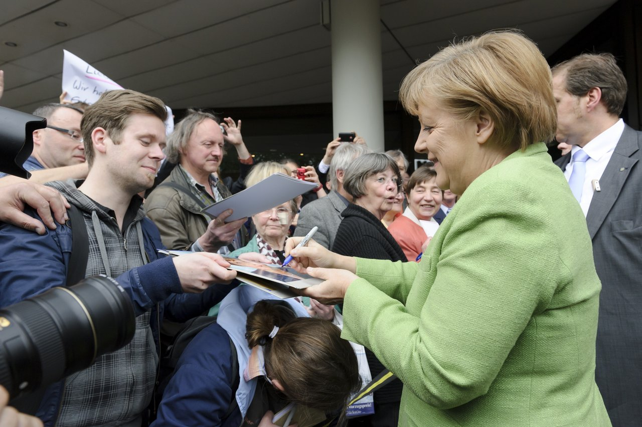 Chancellor Dr. Angela Merkel giving autographs.