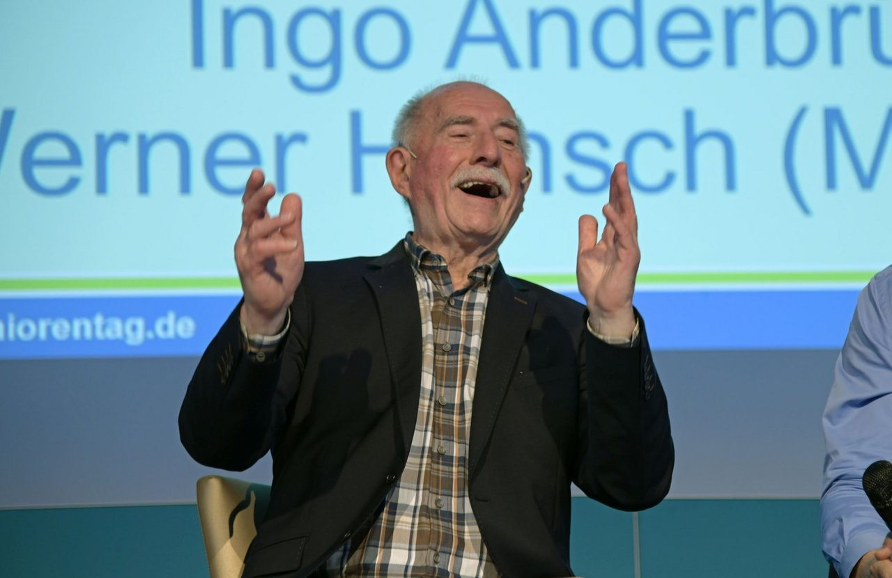Werner Hansch sitting on the stage laughing