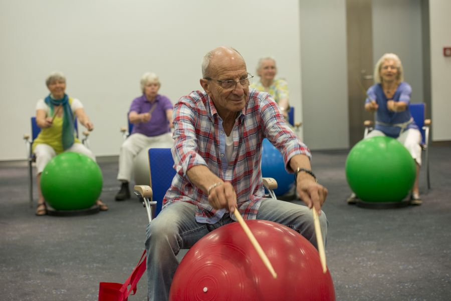 Man drumming on an exercise ball