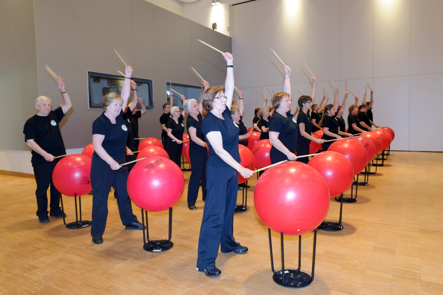 Group picture of persons drumming on an exercise ball