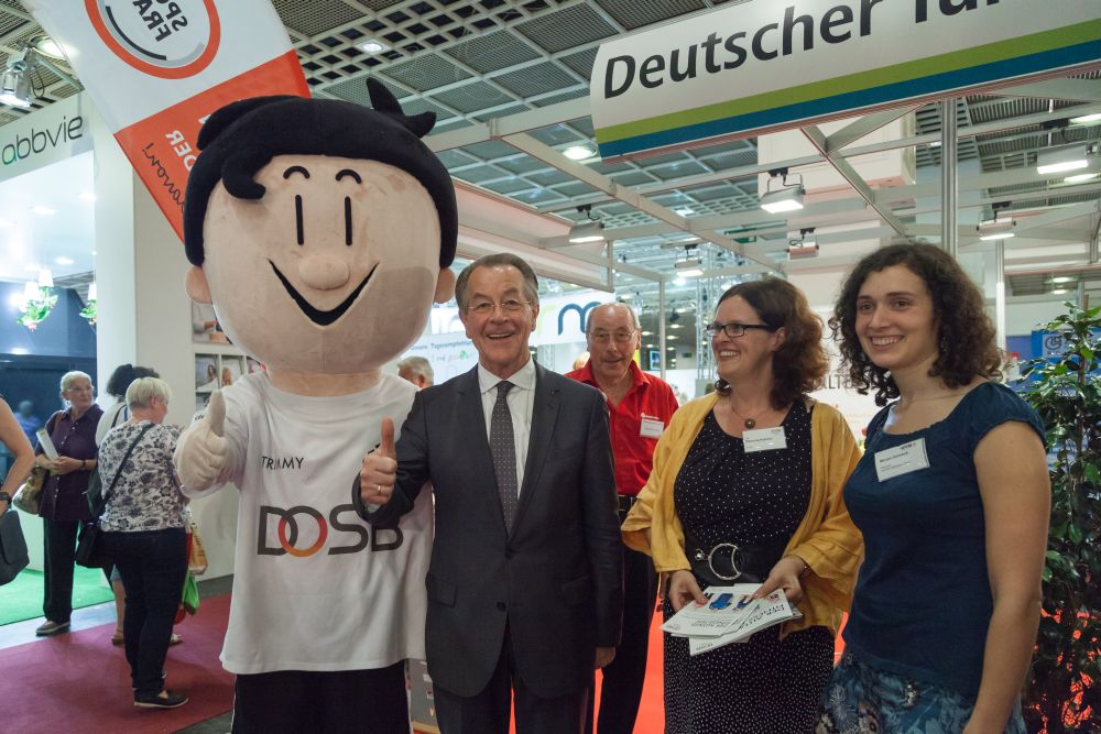 Franz Müntefering standing with the maskot of the German Olympic Sports Confederation an two women